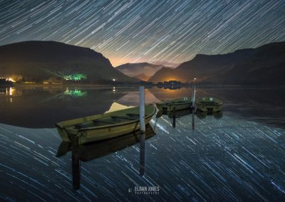 A nightscape startrail image of a frozen lake with Sonwdon and its surrounding mountains reflecting across the calm waters | Elgan Jones Photography